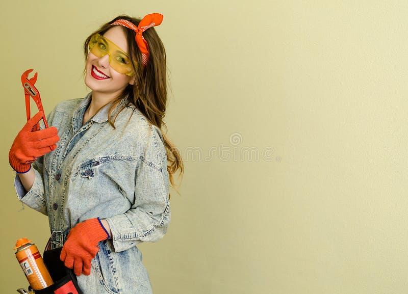 Retrato de la vendedora atractiva con el pelo rubio largo y los vidrios amarillos en tienda de las mejoras para el hogar con los  imágenes de archivo libres de regalías