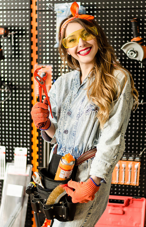 Retrato de la vendedora atractiva con el pelo rubio largo y los vidrios amarillos en tienda de las mejoras para el hogar con los  imagen de archivo