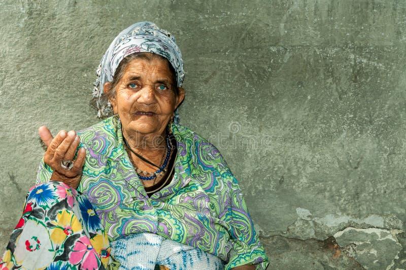 Retrato de la vieja mujer gitana sin hogar del mendigo con la piel arrugada de la cara que pide dinero en la calle en la ciudad y imagen de archivo