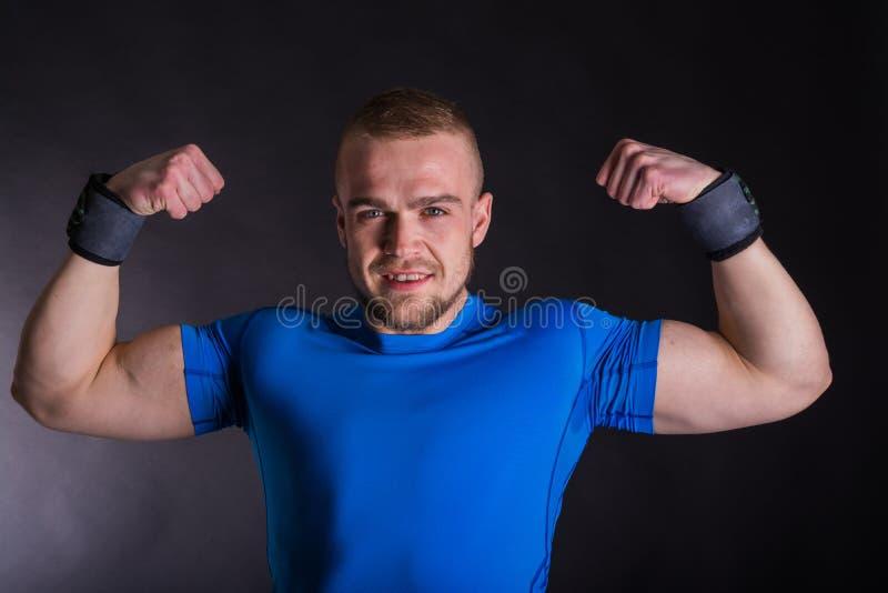 Retrato de la vista delantera de un hombre joven sonriente del atleta que se coloca con los brazos para arriba sobre fondo oscuro imagenes de archivo