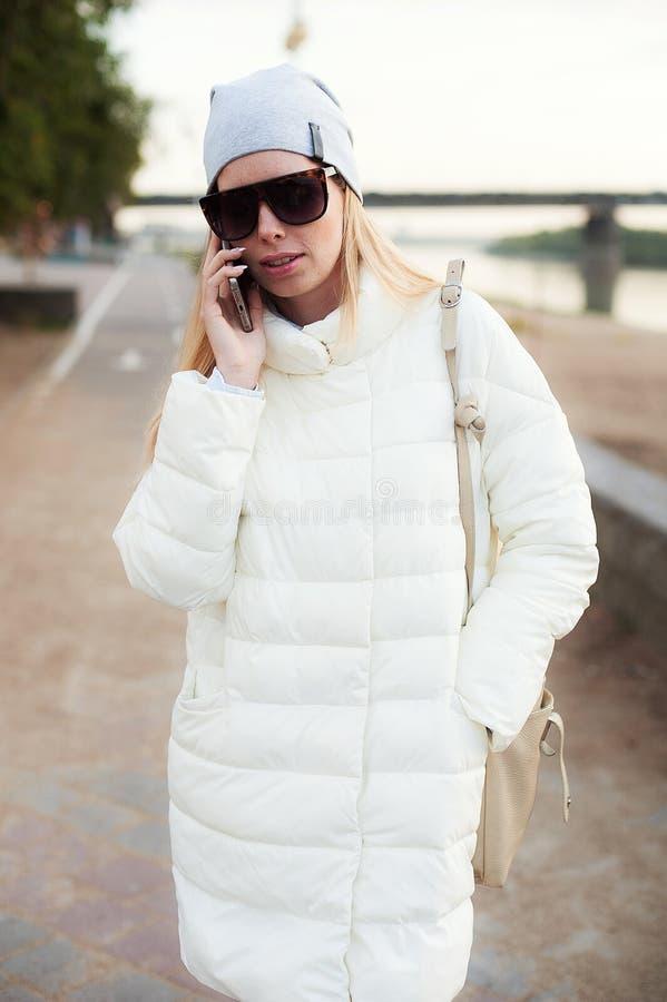 Retrato de la vista delantera de la mujer joven que invita al smartphone que camina hacia cámara en la calle Lookbook de la moda  fotos de archivo libres de regalías