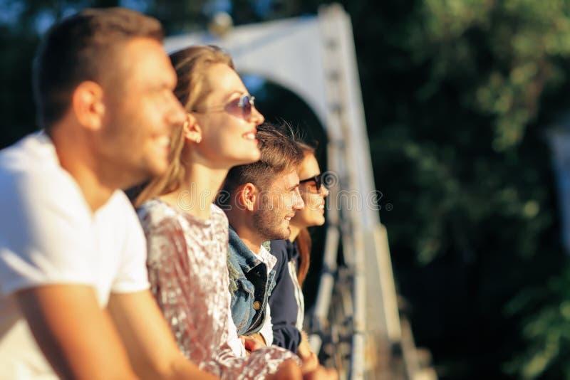 Retrato de la vista lateral de cuatro amigos jovenes que se colocan en el puente fotografía de archivo