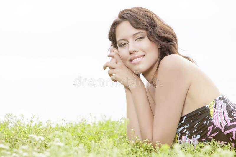 Retrato de la vista lateral de la mujer joven que miente en hierba contra el cielo claro imagen de archivo