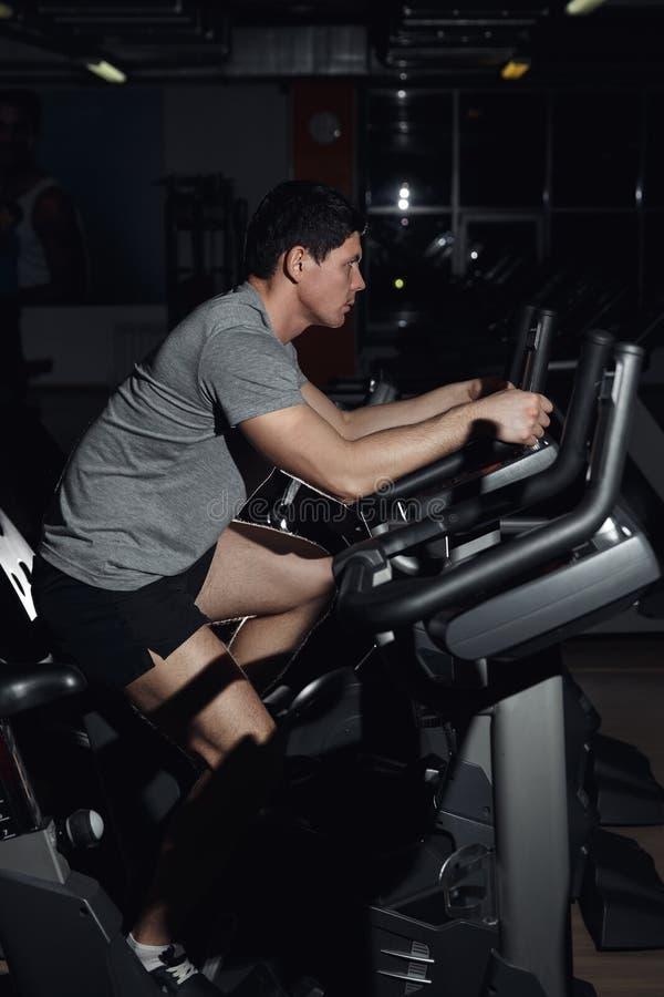 Retrato de la vista lateral de un entrenamiento del hombre en una máquina de la aptitud en el gimnasio fotos de archivo libres de regalías
