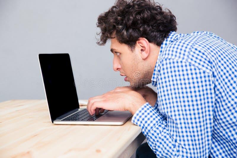 Retrato de la vista lateral de un hombre que usa el ordenador portátil fotos de archivo libres de regalías