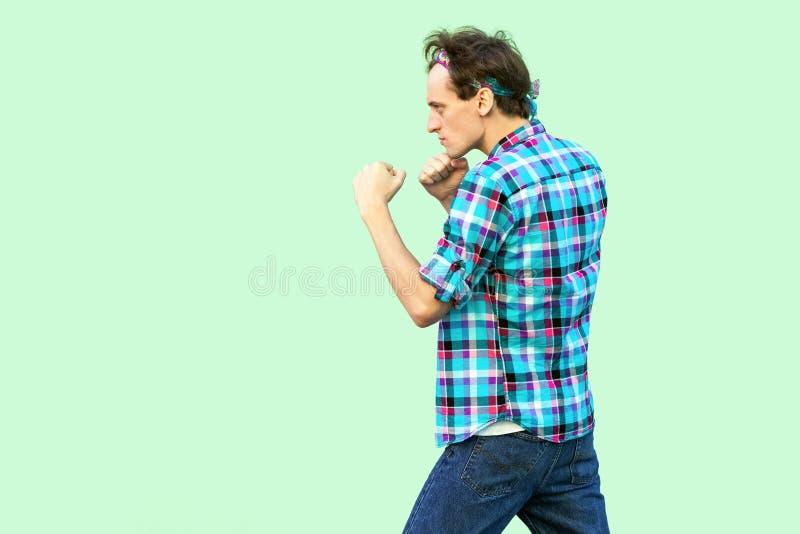 Retrato de la vista lateral del perfil del hombre joven enojado en la situaci?n a cuadros casual de la camisa y de la venda y la  imagen de archivo