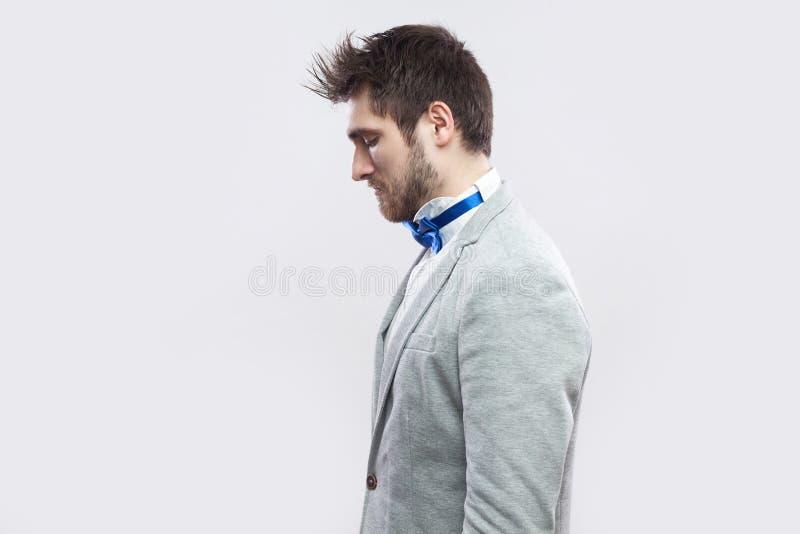 Retrato de la vista lateral del perfil solamente del hombre barbudo hermoso en traje gris casual y la situación azul de la corbat fotografía de archivo