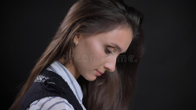 Retrato de la vista lateral del primer de la cara femenina caucásica linda joven con el pelo moreno que mira abajo con el fondo a fotografía de archivo libre de regalías