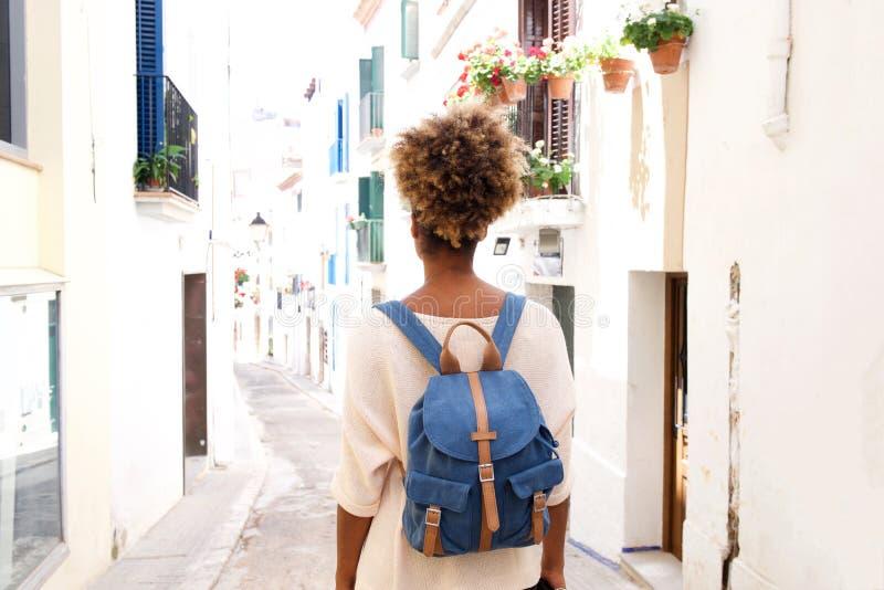 Retrato de la vista posterior de la mujer afroamericana que camina en la calle con el bolso imagenes de archivo