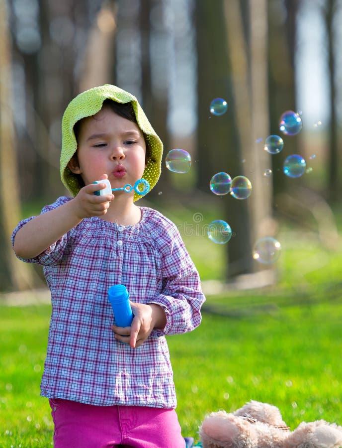 Retrato de las burbujas de jabón de la niña que soplan preciosa divertida en el parque imagenes de archivo