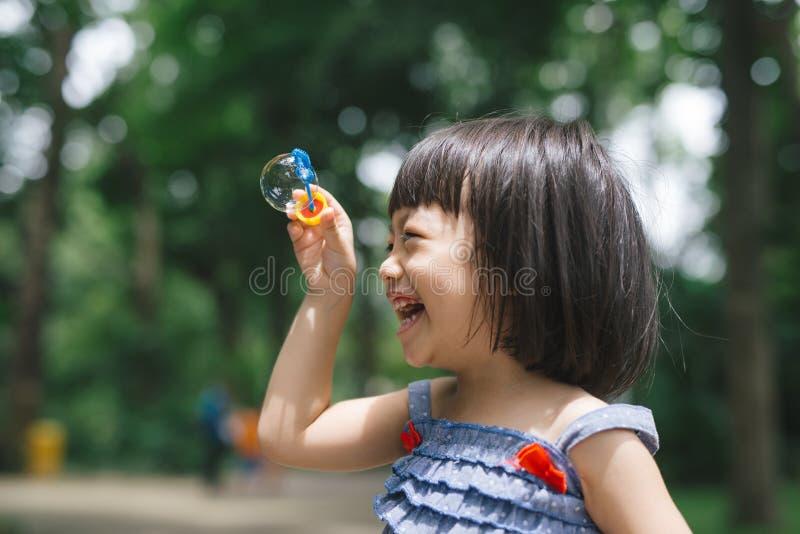 Retrato de las burbujas de jabón de la niña que soplan preciosa divertida imagen de archivo libre de regalías