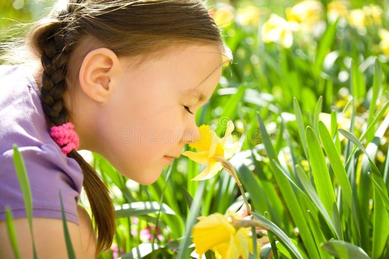 Retrato de las flores que huelen de una niña linda imagen de archivo