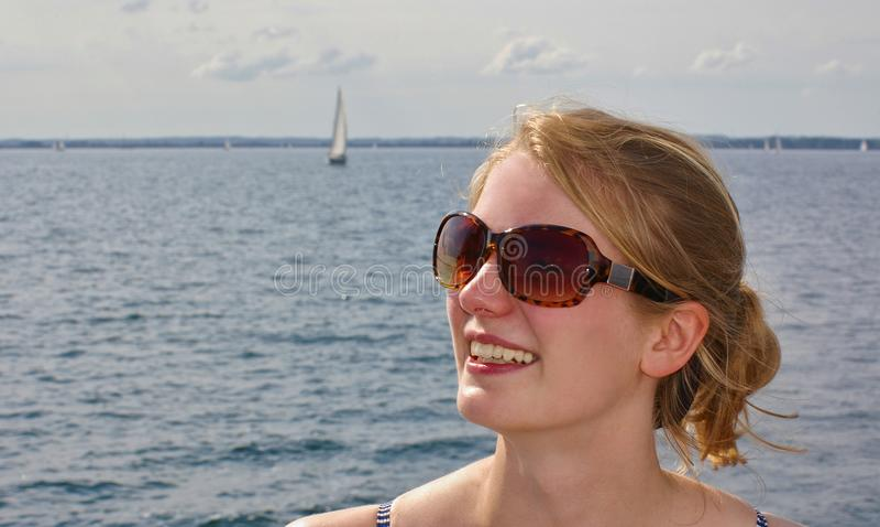 Retrato de las gafas de sol que llevan hermosas de una mujer joven con el mar y un velero distante en el fondo foto de archivo