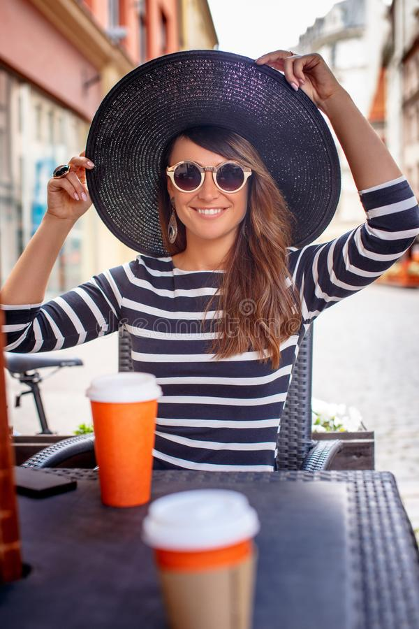Retrato de las gafas de sol que llevan jovenes de una mujer de moda y del sombrero elegante que se sientan en un café de la calle fotos de archivo
