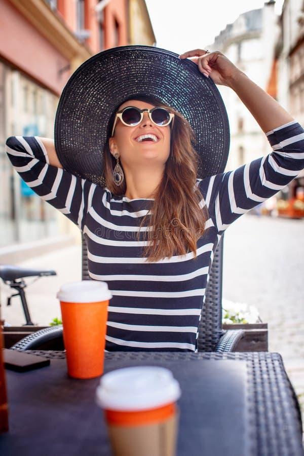Retrato de las gafas de sol que llevan jovenes de una mujer de moda y del sombrero elegante que se sientan en un café de la calle fotografía de archivo