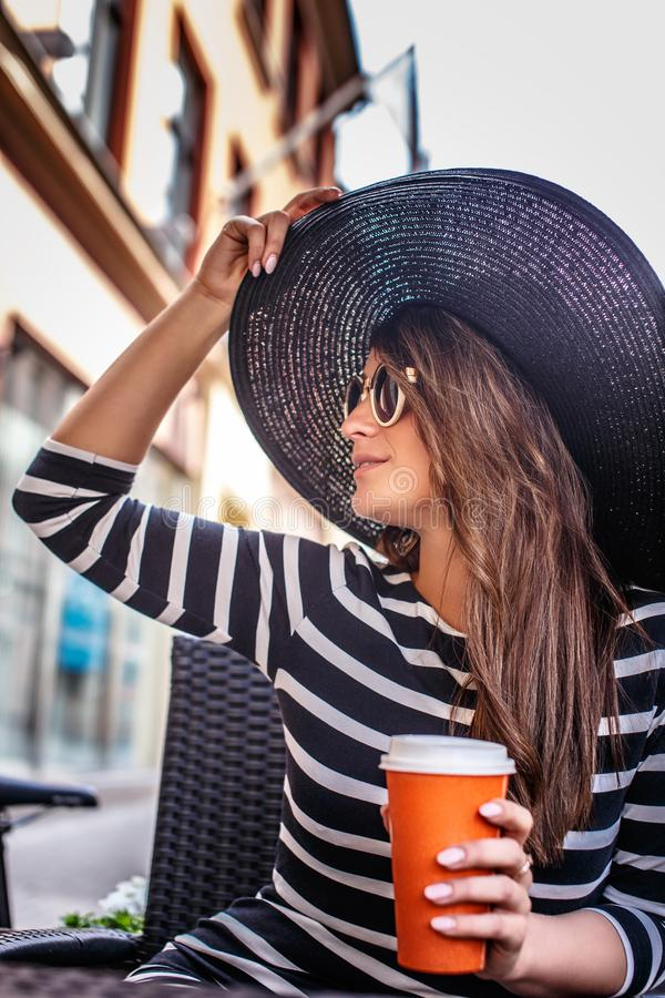 Retrato de las gafas de sol que llevan jovenes de una mujer de moda y del sombrero elegante que se sientan en un café de la calle foto de archivo
