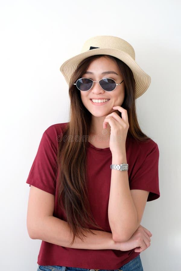 Retrato de las gafas de sol que llevan y del sombrero de la mujer asiática linda joven que sonríen sobre el fondo blanco de la pa foto de archivo libre de regalías