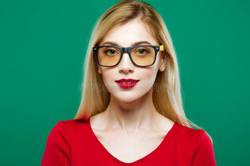 Retrato de las lentes que llevan de la muchacha linda en fondo verde Mujer joven con los labios sensuales rojos y el pelo largo e imágenes de archivo libres de regalías