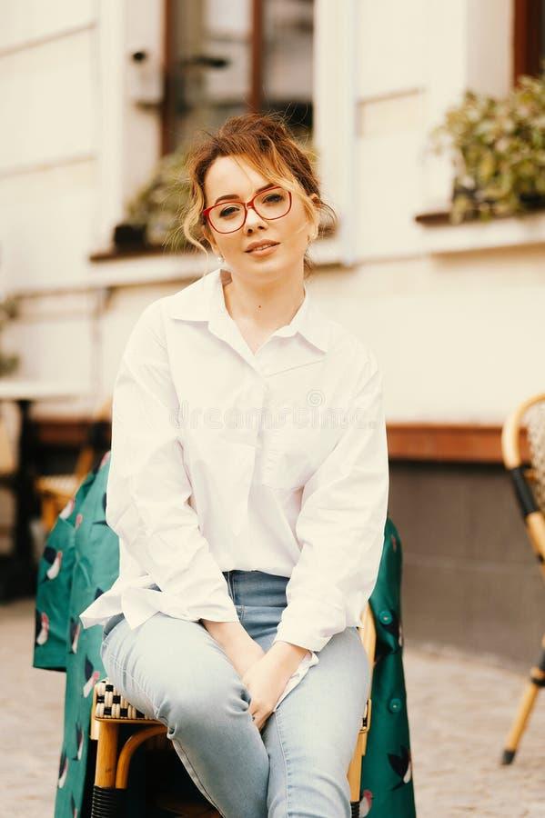 Retrato de las lentes que llevan de la mujer rubia atractiva joven imagen de archivo libre de regalías