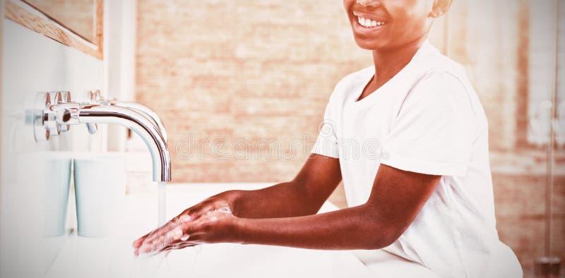 Retrato de las manos que se lavan sonrientes del muchacho en fregadero imagen de archivo libre de regalías