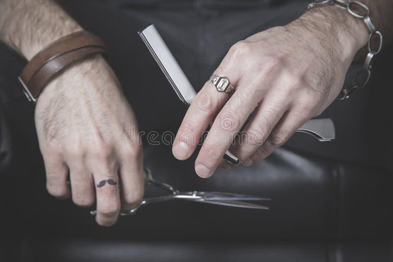 Retrato de las manos de un peluquero que sostiene una maquinilla de afeitar y tijeras foto de archivo libre de regalías