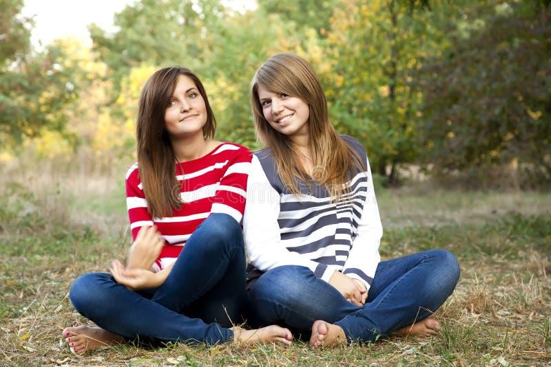 Retrato de las muchachas del redhead y del brunette en al aire libre. fotos de archivo libres de regalías