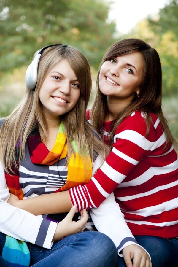 Retrato de las muchachas del redhead y del brunette en al aire libre. fotos de archivo