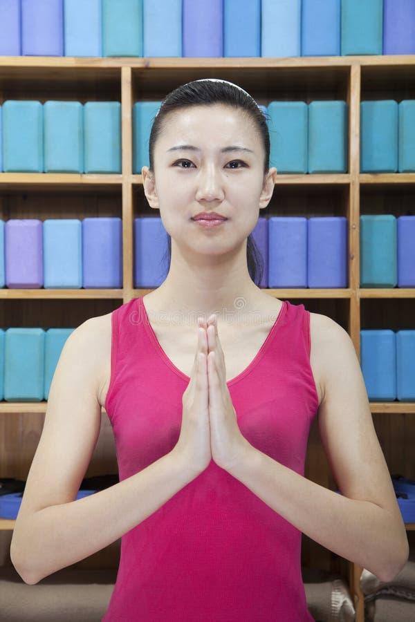 Retrato de las mujeres jovenes que hacen yoga con las manos abrochadas juntas, mirando la cámara imagenes de archivo