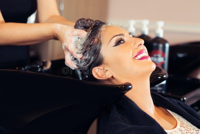 Retrato de las mujeres que lavan el pelo en un salón de belleza fotografía de archivo libre de regalías