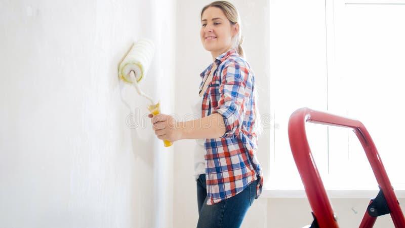 Retrato de las paredes sonrientes de la pintura de la chica joven con la pintura blanca imagen de archivo libre de regalías
