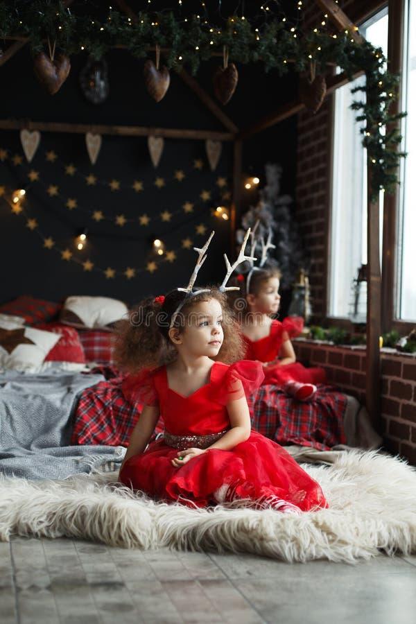 Retrato de las pequeñas muchachas gemelas del thinkfull lindo cerca de la ventana y de parecer exterior Hermanas rizadas en los v fotos de archivo