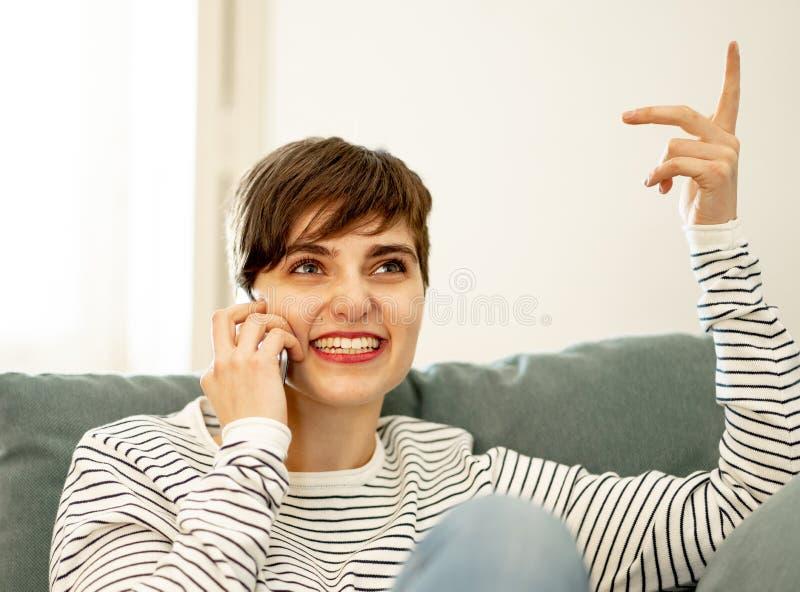 Retrato de ligar que habla de la mujer hermosa joven y de la charla en su tel?fono elegante imagen de archivo
