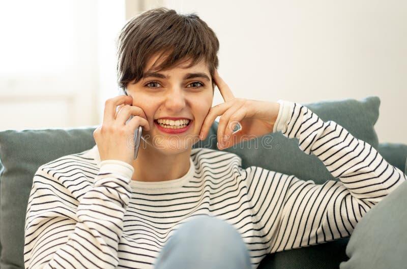 Retrato de ligar que habla de la mujer hermosa joven y de la charla en su tel?fono elegante imagenes de archivo