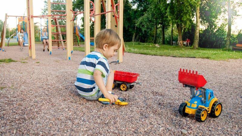 Retrato de los 3 años adorables del niño pequeño que juega con el camión del juguete con el remolque en el patio en el parque Ni? foto de archivo