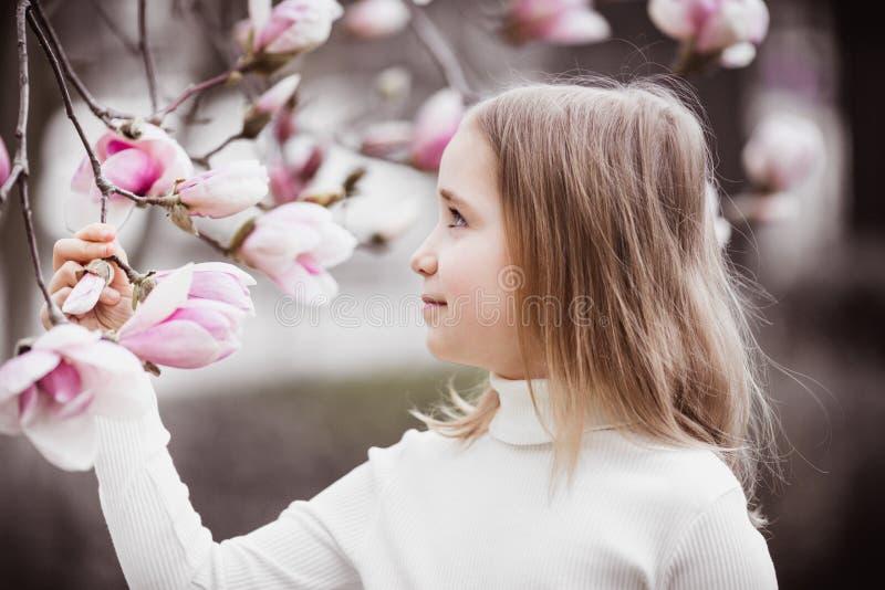 Retrato de los años de la muchacha 8-9 Lleva a cabo una rama de un árbol de la magnolia El árbol florece en flores rosadas grande imagen de archivo