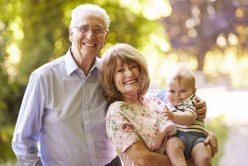 Retrato de los abuelos que caminan adentro al aire libre con el nieto del bebé imagen de archivo libre de regalías