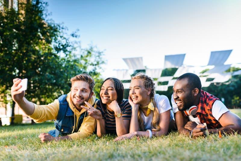 retrato de los amigos alegres multiétnicos que toman el selfie en smartphone mientras que descansa sobre hierba verde fotos de archivo libres de regalías