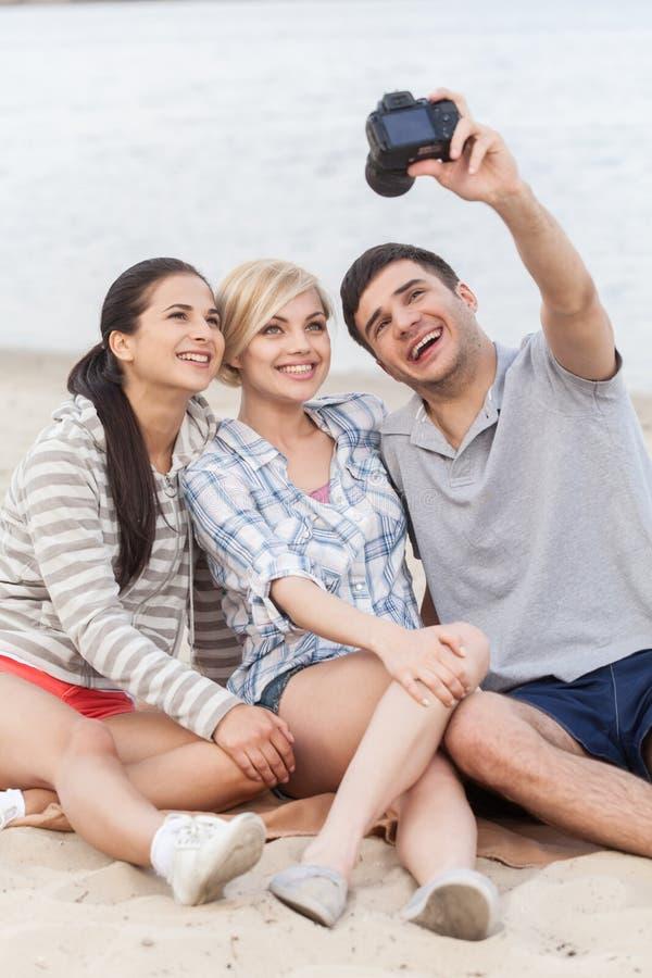 Retrato de los amigos felices que toman la foto de ellos mismos en la playa imagen de archivo libre de regalías