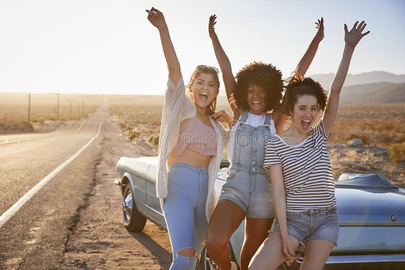 Retrato de los amigos femeninos que disfrutan del viaje por carretera que se coloca al lado del coche clásico en la carretera del fotos de archivo