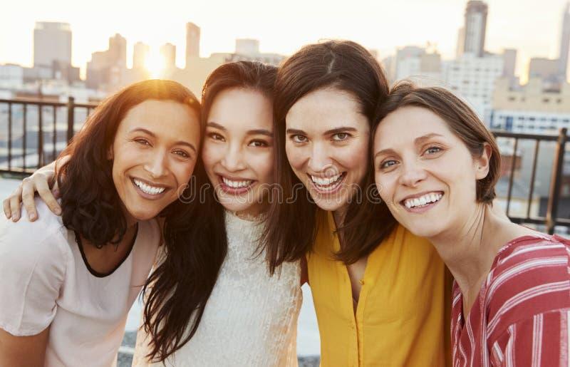 Retrato de los amigos femeninos recolectados en la terraza del tejado para el partido con horizonte de la ciudad en fondo imagenes de archivo