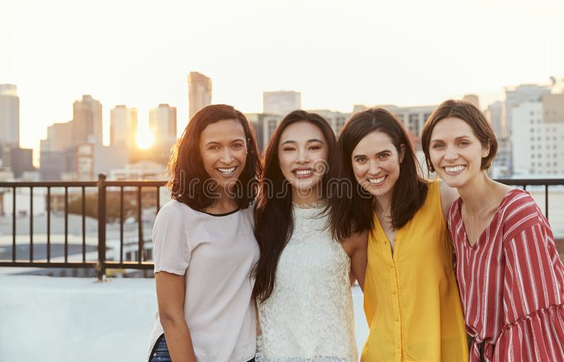 Retrato de los amigos femeninos recolectados en la terraza del tejado para el partido con horizonte de la ciudad en fondo imagen de archivo