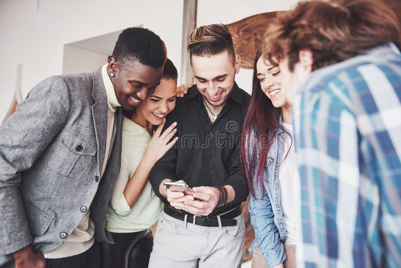 Retrato de los amigos jovenes alegres que miran el teléfono elegante mientras que se sienta en café Gente de la raza mixta en res imagenes de archivo