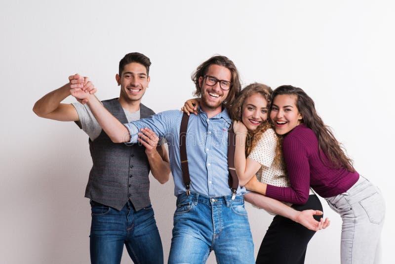 Retrato de los amigos jovenes alegres que se colocan en un estudio, disfrutando de un partido foto de archivo