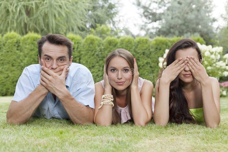 Retrato de los amigos jovenes que cubren la boca, los oídos y los ojos en parque fotografía de archivo
