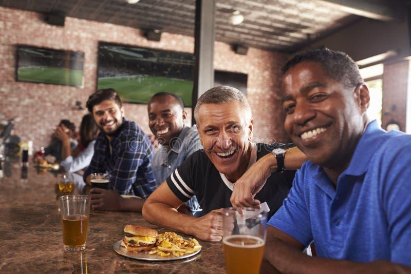 Retrato de los amigos masculinos en el contador en barra de deportes foto de archivo