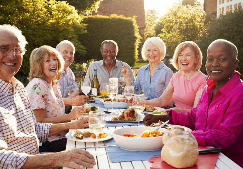 Retrato de los amigos mayores que disfrutan del partido de cena al aire libre en casa imágenes de archivo libres de regalías