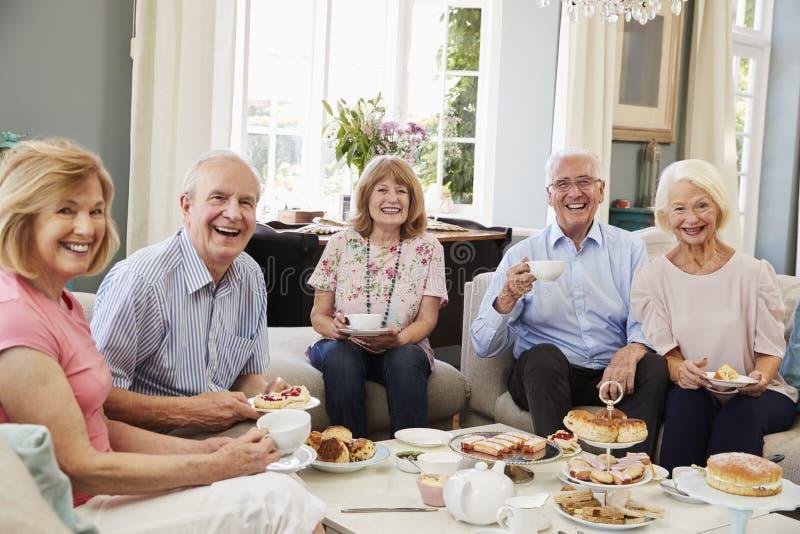 Retrato de los amigos mayores que gozan de té de tarde en casa foto de archivo