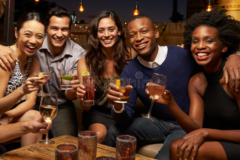 Retrato de los amigos que disfrutan de noche hacia fuera en la barra del tejado imagenes de archivo
