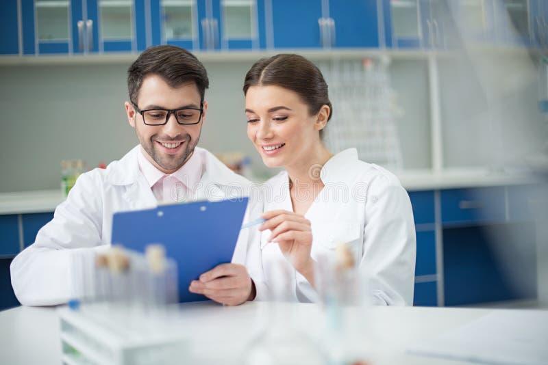 Retrato de los científicos sonrientes que escriben en libreta foto de archivo