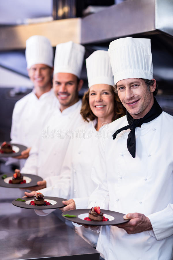 Retrato de los cocineros felices que presentan sus placas de postre foto de archivo libre de regalías